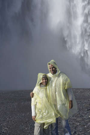 waterproof cape: Couple wearing rain ponchos in front of waterfall LANG_EVOIMAGES