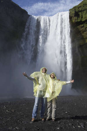 Couple wearing rain ponchos in front of waterfall Stock Photo - 16092183