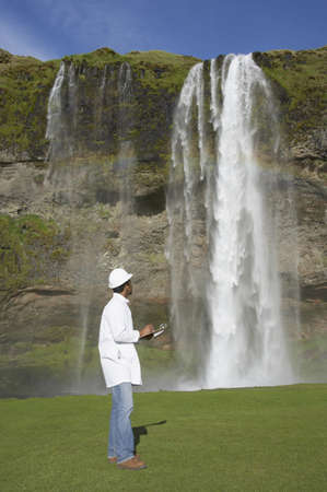 Man with hard hat and clipboard looking at waterfall Stock Photo - 16092184