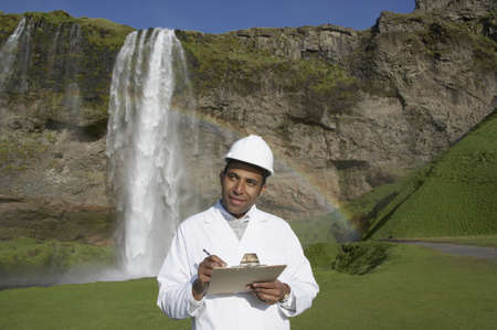 Man with hard hat and clipboard in front of waterfall Stock Photo - 16092188