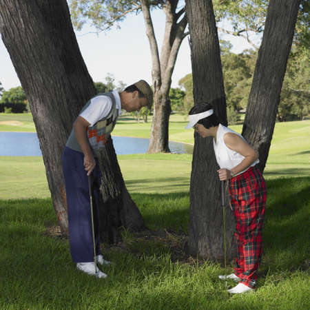 finding a mate: Senior Asian couple looking at bad lie on golf course