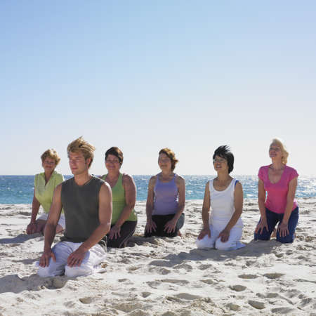 medium group of people: Group of women practicing yoga with instructor on beach