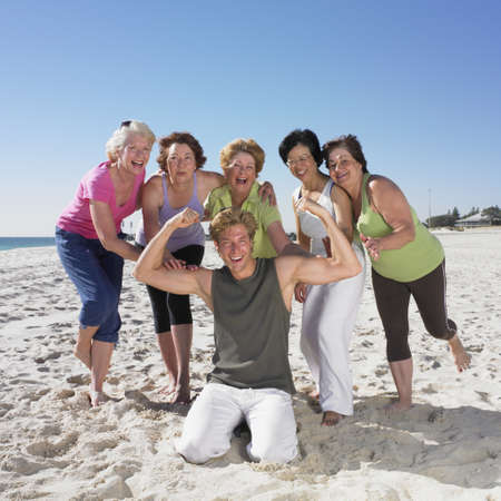 athletic gear: Group of senior women in athletic gear with young man on beach