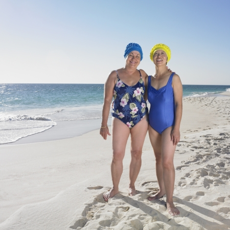 Two senior women in bathing suits smiling on beach