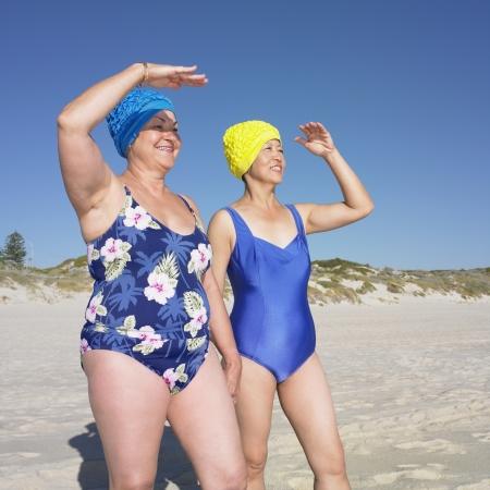 Twee senior vrouwen in badpak schaduw hun ogen op het strand