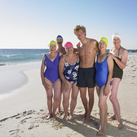pastimes: Group of senior women in bathing suits with young man at beach LANG_EVOIMAGES