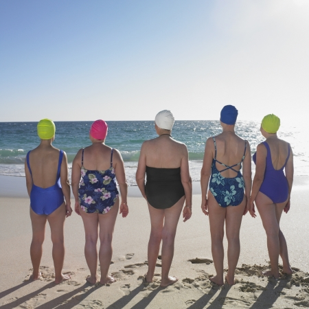 medium group of people: Rear view of women in bathing suits at beach LANG_EVOIMAGES
