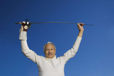 low spirited: Senior male fencer holding epee above head
