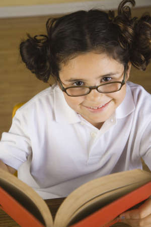 literacy instruction: Hispanic girl wearing eye glasses and reading book