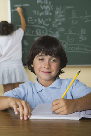 schoolmate: Boy writing in notebook while girl writes on blackboard in classroom LANG_EVOIMAGES