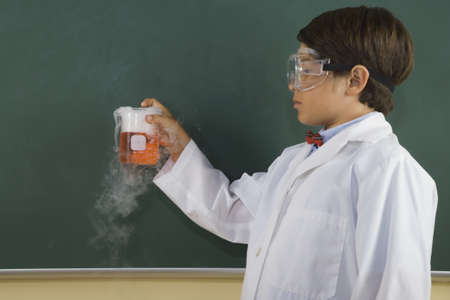 jeopardizing: Boy wearing lab coat and goggles and holding steaming beaker in classroom