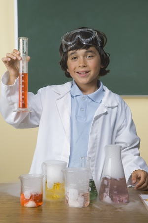Young boy in science class holding beaker 스톡 콘텐츠