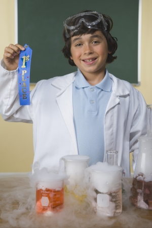 jeopardizing: Young boy with science project holding first place ribbon