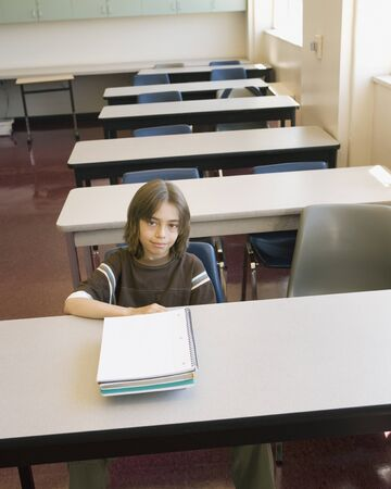 Boy sitting at desk in empty classroom Stock Photo - 16092230