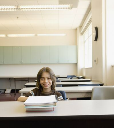 Boy sitting at desk in empty classroom Stock Photo