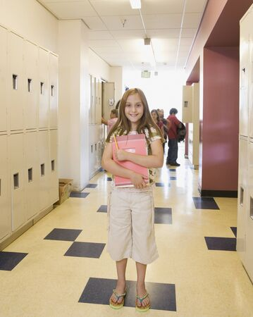 corridors: Girl holding notebook in school hallway LANG_EVOIMAGES