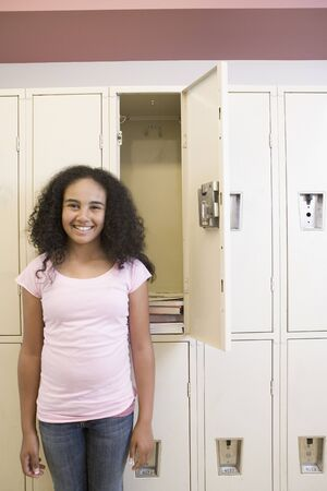 African girl standing next to open school locker Stock Photo - 16092233