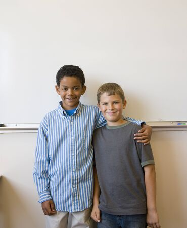schoolmate: Two boys standing in front of whiteboard LANG_EVOIMAGES