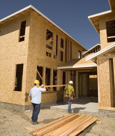 work from home: Two construction workers carrying lumber into unfinished building
