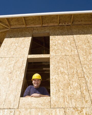 Construction worker looking out of window in unfinished building Stock Photo - 16092245