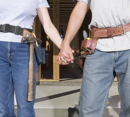 Couple holding hands and wearing tool belts Stock Photo - 16092247