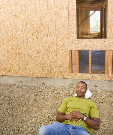 wearying: Male construction worker sleeping at construction site