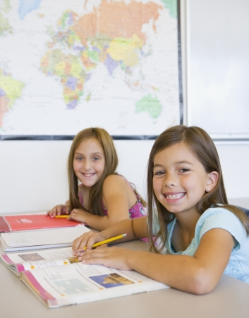 front desk: Two girls smiling at desk in classroom