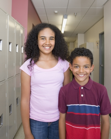 Girl and boy smiling in school hallway