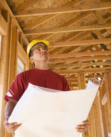 Male construction worker holding blueprints inside construction site Stock Photo - 16092260