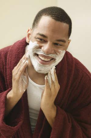 red bathrobe: African man applying shaving cream to face LANG_EVOIMAGES
