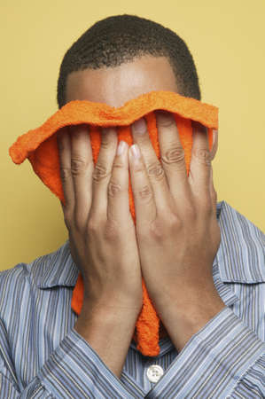 African man in pajamas holding washcloth to face Stock Photo - 16092269
