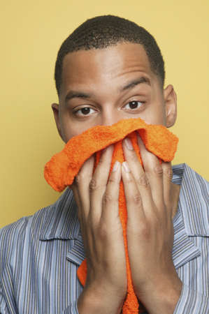 washcloth: African man in pajamas holding washcloth to face
