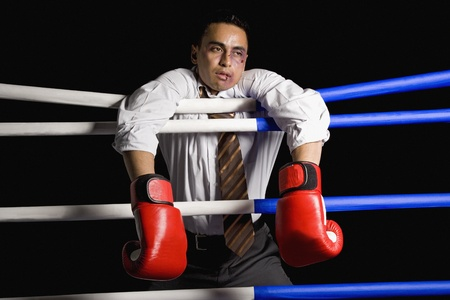 Bruised businessman hanging on ropes in boxing ring Stock Photo