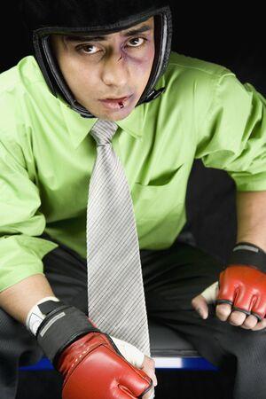 endangering: Bruised businessman wearing sparring gloves and helmet