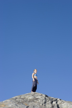 jeopardizing: Low angle view of woman standing on top of mountain LANG_EVOIMAGES