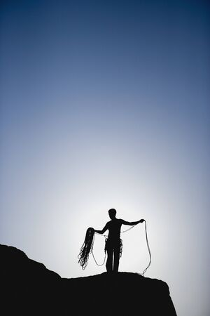 jeopardizing: Silhouette of rock climber with rope on mountain