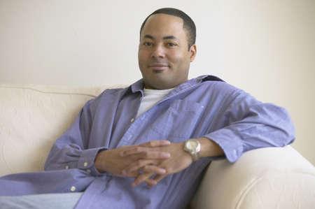 davenport: African man sitting on sofa smiling