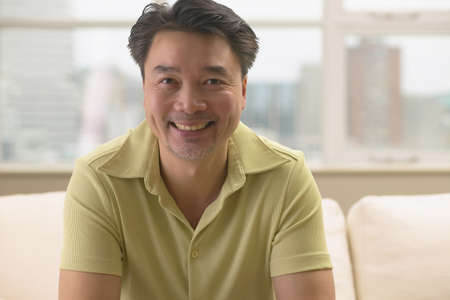 davenport: Asian man smiling on sofa