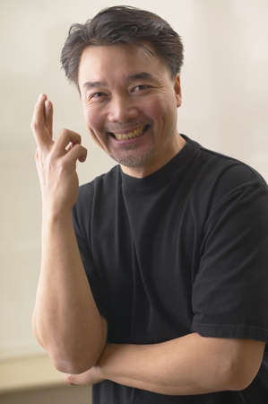 Asian man smiling and crossing fingers Stock Photo - 16092301