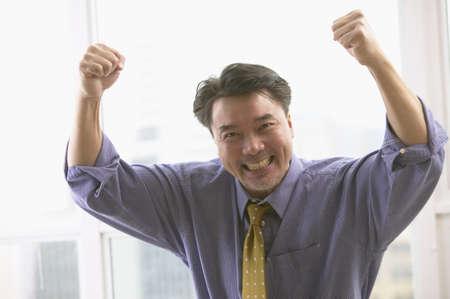 relishing: Asian businessman cheering LANG_EVOIMAGES