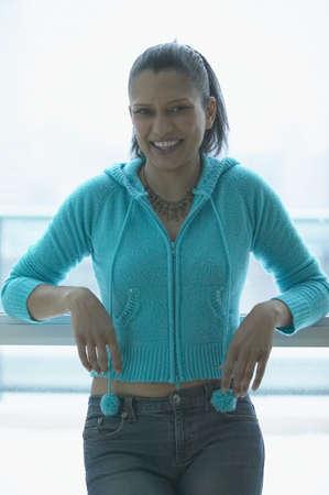 casualness: Asian woman smiling and leaning on railing