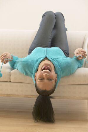 relishing: Woman upside down on sofa laughing LANG_EVOIMAGES