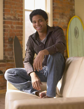 casualness: Young African man sitting on arm of sofa smiling