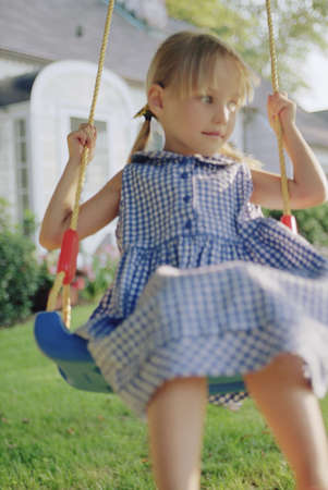 idealistic: Young girl on swing in yard
