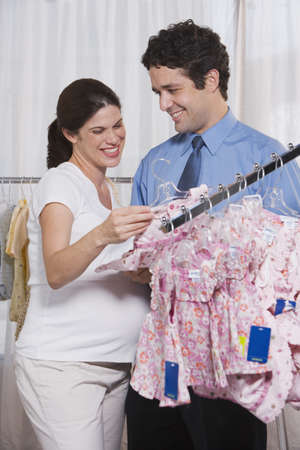 finding a mate: Pregnant Woman and Husband Shopping for Baby Clothes