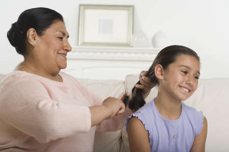 Hispanic grandmother brushing granddaughter's hair Stock Photo - 16092363