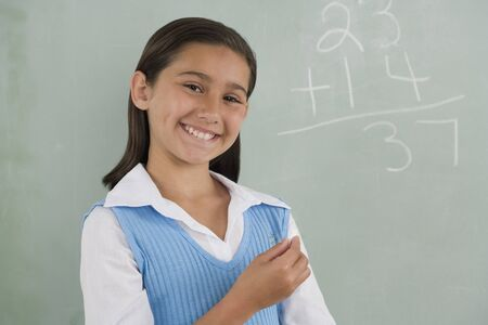 Hispanic girl smiling in front of blackboard Stock Photo - 16092371