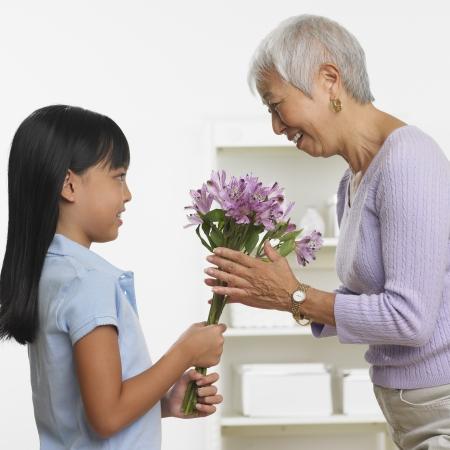 Asian girl giving grandmother bouquet of flowers Standard-Bild