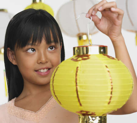 lamp shade: Young Asian girl holding paper lantern