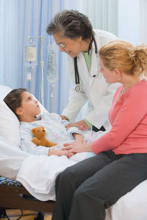 sick teddy bear: Senior female doctor talking to girl in hospital bed LANG_EVOIMAGES